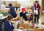 Volunteers pack food boxes for families at The South Congregational Church Food Pantry, Wednesday, May 20, 2020, in Pittsfield, Mass. All the food distribution is carefully packed and transferred without contact. (Ben Garver/The Berkshire Eagle via AP)