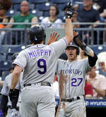 Colorado Rockies' Daniel Murphy (9) is greeted by Trevor Story (27) after crossing home plate on a three-run home run off Pittsburgh Pirates starting pitcher Montana DuRapau during the first inning of a baseball game in Pittsburgh, Wednesday, May 22, 2019. (AP Photo/Gene J. Puskar)