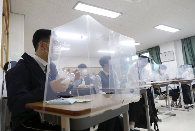 Senior students wait for a class to begin with plastic shields placed on their desks at Jeonmin High School in Daejeon, South Korea, Wednesday, May 20, 2020. South Korean students began returning to schools Wednesday as their country prepares for a new normal amid the coronavirus pandemic. (Kim Jun-beom/Yonhap via AP)