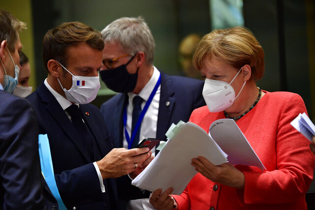 French President Emmanuel Macron, second left, speaks with German Chancellor Angela Merkel during a round table meeting at an EU summit in Brussels, Monday, July 20, 2020. Weary European Union leaders are expressing cautious optimism that a deal is in sight on their fourth day of wrangling over an unprecedented budget and coronavirus recovery fund. (John Thys, Pool Photo via AP)