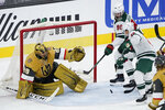 Minnesota Wild defenseman Jared Spurgeon, right, attempts a shot on Vegas Golden Knights goaltender Marc-Andre Fleury (29) during the second period of an NHL hockey game Saturday, April 3, 2021, in Las Vegas. (AP Photo/John Locher)