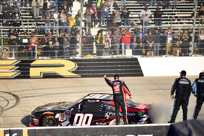 Driver Cole Custer of the (00) car spins out near the finish line as some of his team celebrates after winning the 34th Annual Use You Melon Drive Sober 200 during the  NASCAR Xfinity Series auto race, Saturday, Oct. 5, 2019, in Dover, Del. (AP Photo/Brien Aho)