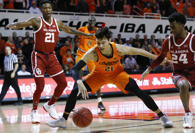 Oklahoma State guard Lindy Waters III, center, and Oklahoma forward Kristian Doolittle, left, and guard Jamal Bieniemy (24) watch a loose ball during the first half of an NCAA college basketball game in Stillwater, Okla., Wednesday, Jan. 23, 2019. (AP Photo/Sue Ogrocki)