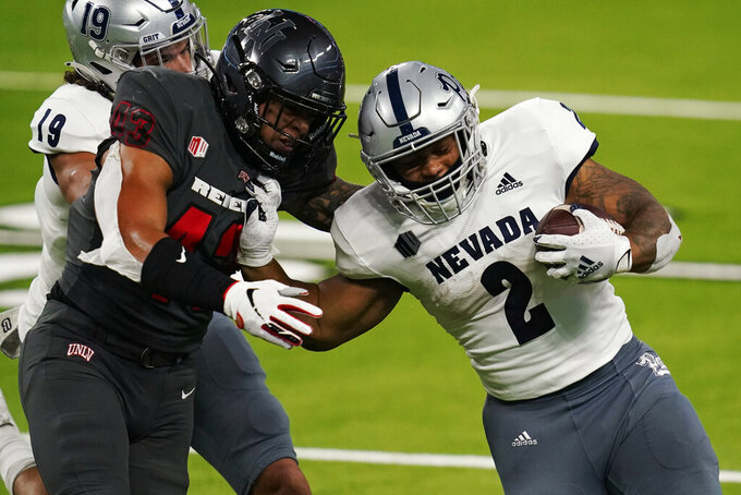 Nevada running back Devonte Lee (2) runs for a gain around UNLV linebacker Malakai Salu (43) during the first half of an NCAA college football game Saturday, Oct. 31, 2020, in Las Vegas. (AP Photo/John Locher)