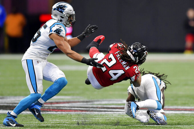 Carolina Panthers strong safety Eric Reid, left and Carolina Panthers cornerback Donte Jackson (26) hit Atlanta Falcons running back Devonta Freeman (24) during the first half of an NFL football game, Sunday, Dec. 8, 2019, in Atlanta. (AP Photo/Mike Stewart)