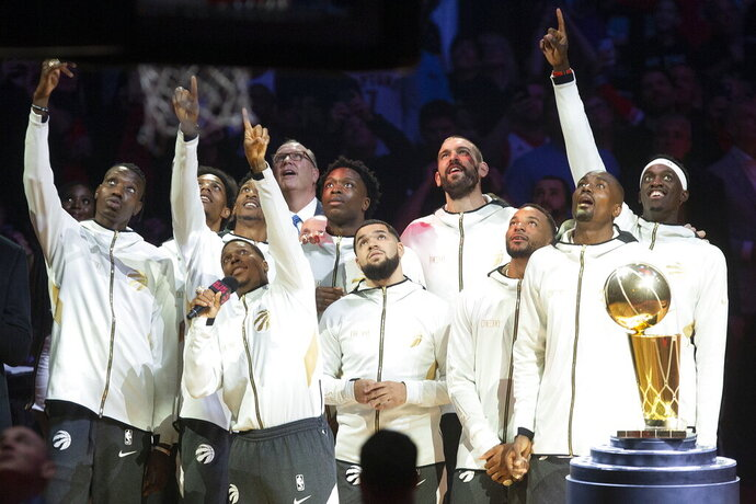 Toronto Raptors watch their 2019 NBA basketball championship pennant being raised before the team's game against the New Orleans Pelican on Tuesday, Oct. 22, 2019, in Toronto. (Chris Young/The Canadian Press via AP)