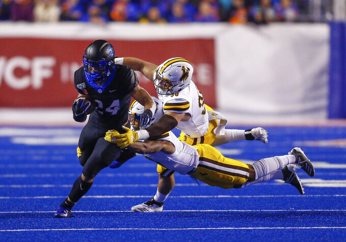 Boise State running back George Holani, left, tries to break away from two Wyoming defenders during the first half of an NCAA college football game Saturday, Nov. 9, 2019, in Boise, Idaho. (AP Photo/Steve Conner)