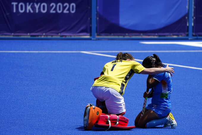 Britain's goalkeeper Claire Hinch (1) comforts India's Neha Neha, right, after winning their women's field hockey bronze medal match at the 2020 Summer Olympics, Friday, Aug. 6, 2021, in Tokyo, Japan. Britain won 4-3. (AP Photo/John Minchillo)
