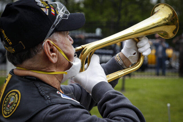 A bugler plays Taps as a motorcade of veterans stops outside the VA Medical Center for a wreath laying ceremony beside memorial stones on the premises, Monday, May 25, 2020, in the Brooklyn borough of New York. (AP Photo/John Minchillo)