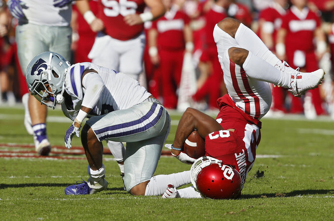 Oklahoma wide receiver Nick Basquine, right, tumbles after a tackle by Kansas State defensive back Walter Neil Jr., left, in the first half of an NCAA college football game in Norman, Okla., Saturday, Oct. 27, 2018. (AP Photo/Sue Ogrocki)