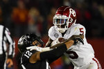 Oklahoma running back T.J. Pledger (5) is tackled by Iowa State defensive back Greg Eisworth II (12) during the first half an NCAA college football game, Saturday, Oct. 3, 2020, in Ames, Iowa. (AP Photo/Charlie Neibergall)