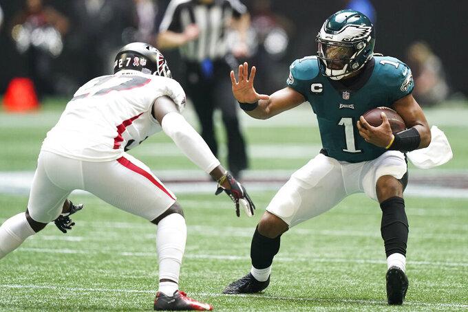 Philadelphia Eagles quarterback Jalen Hurts (1) runs near Atlanta Falcons safety Richie Grant (27) during the second half of an NFL football game, Sunday, Sept. 12, 2021, in Atlanta. (AP Photo/Brynn Anderson)