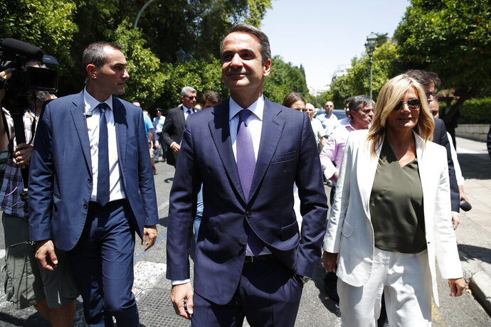 Greek opposition New Democracy conservative party leader Kyriakos Mitsotakis centre, walks with his wife Mareva, right in Athens, Monday, July 8, 2019. Mitsotakis was to be sworn in as Greece's new prime minister after a resounding win over left-wing Alexis Tsipras, who led the country through the tumultuous final years of its international bailouts. Mitsotakis' New Democracy party won 39.8% of the vote, giving him 158 seats in the 300-member parliament, a comfortable governing majority. (AP Photo/Thanassis Stavrakis)