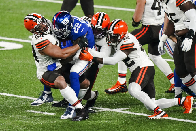 Cleveland Browns' Olivier Vernon (54) tackles New York Giants' Wayne Gallman (22) with teammates during the first half of an NFL football game Sunday, Dec. 20, 2020, in East Rutherford, N.J. (AP Photo/Corey Sipkin)