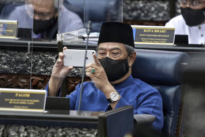 In this picture release by Malaysia Information Ministry show Malaysian Prime Minister Muhyiddin Yassin taking pictures with his mobile phone before Minister Finance Minister Zafrul Aziz, not show, deliver the 2021 budget speech at parliament in Kuala Lumpur, Malaysia, Friday, Nov. 6, 2020. (Khirul Nizam Zanil/Malaysia's Department of Information via AP)