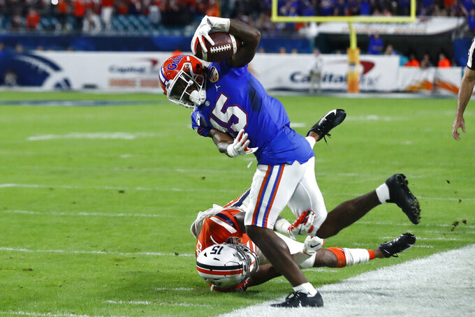 CORRECTS TO COPELAND MAKES A CATCH NOT SCORES A TOUCHDOWN - Florida wide receiver Jacob Copeland (15) makes a catch over Virginia safety De'Vante Cross, bottom, during the first half of the Orange Bowl NCAA college football game, Monday, Dec. 30, 2019, in Miami Gardens, Fla. (AP Photo/Brynn Anderson)