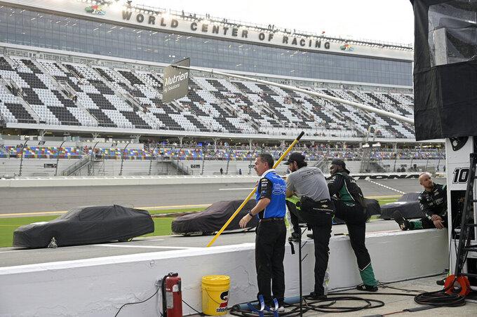 Crew members of the Jeb Burton team stand along the pit road wall during a weather delay in NASCAR Xfinity Series auto race at Daytona International Speedway, Friday, Aug. 27, 2021, in Daytona Beach, Fla. (AP Photo/Phelan M. Ebenhack)