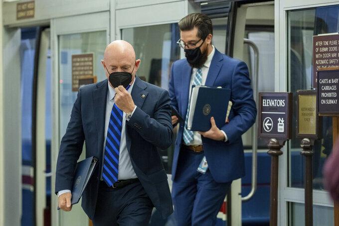 Sen. Mark Kelly, D-Ariz., adjusts his mask as he leaves the Senate subway on Capitol Hill in Washington, Tuesday, Aug. 3, 2021. (AP Photo/Amanda Andrade-Rhoades)