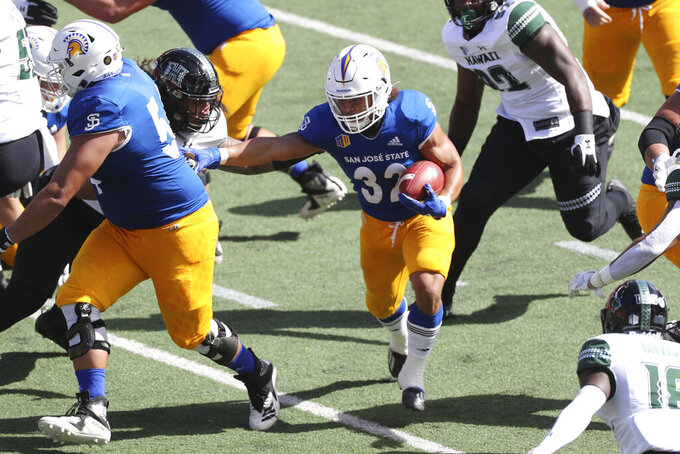 San Jose State running back Kairee Robinson (32) runs through the Hawaii defense in the first half of an NCAA college football game Saturday, Dec. 5, 2020, in Honolulu. (AP Photo/Marco Garcia)