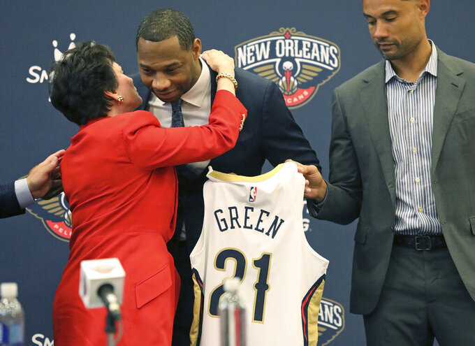Willie Green gets a hug from New Orleans Pelicans Governor Gayle Benson after he was introduced as the new head coach for the New Orleans Pelicans NBA basketball team, in Metairie, La., Tuesday, July 27, 2021. At right is Pelicans General Manager Trajan Langdon. (AP Photo/Ted Jackson)