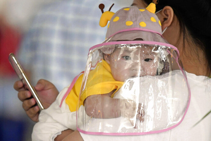 A baby with a face shield waits to board a plane at an airport in Wuhan, central China's Hubei Province Saturday, May 23, 2020. China on Saturday reported no new confirmed cases or deaths from the new coronavirus. (Kyodo News via AP)