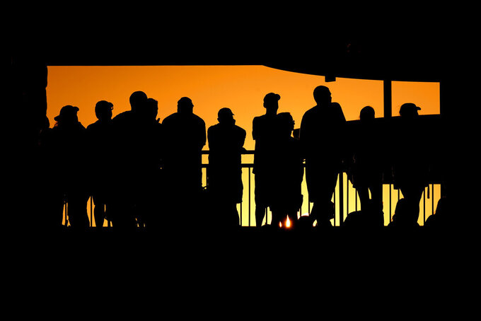 Fans are silhouetted by the setting sun as they watch during the first half of an NCAA college football game between Kansas State and Southern Illinois, Saturday, Sept. 11, 2021, in Manhattan, Kan. (AP Photo/Charlie Riedel)