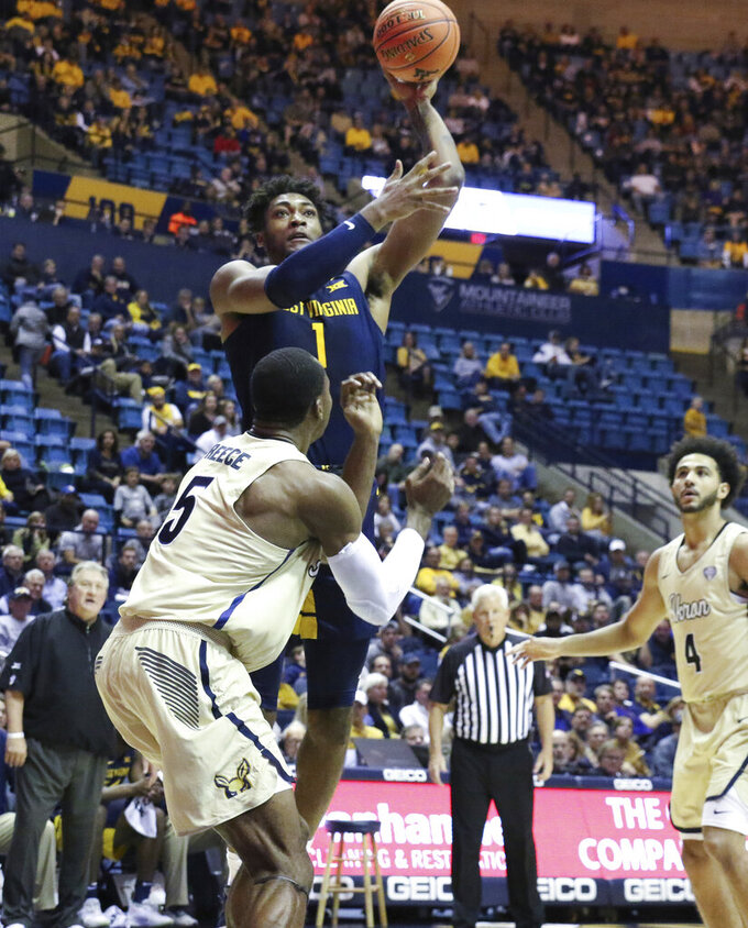 West Virginia's Derek Culver shoots over Akron's Camron Reece during an NCAA college basketball game Friday, Nov. 8, 2019, in Morgantown, W.Va. (AP Photo/Kathleen Batten)