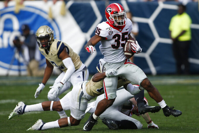 Georgia running back Brian Herrien (35) tries to break a tackle from Georgia Tech defensive back Jaylon King (14) in the second half during an NCAA college football game Saturday, Nov. 30, 2019, in Atlanta. (Joshua L. Jones/Athens Banner-Herald via AP)