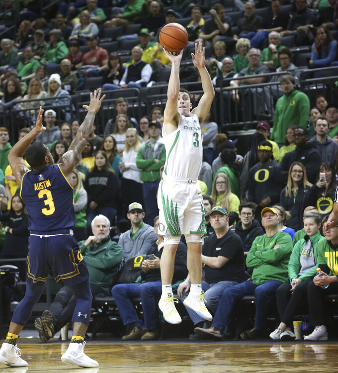 Oregon's Payton Pritchard, right, shoots a 3-pointerover California's Paris Austin, left, during the first half of an NCAA college basketball game Wednesday, Feb. 6, 2019, in Eugene, Ore. (AP Photo/Chris Pietsch)