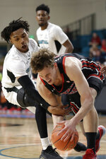 Coastal Carolina guard Christian Adams, left, pressures Utah forward Mikael Jantunen during the first half of an NCAA college basketball game at the Myrtle Beach Invitational in Conway, S.C., Thursday, Nov. 21, 2019. (AP Photo/Gerry Broome)