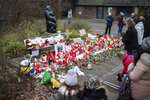 A women lights a candle at the main entrance of the Zoo in Krefeld, Germany, Thursday, Jan. 2, 2020. Three woman are under investigation for launching paper sky lanterns blamed for setting off a fire that destroyed an ape house at the zoo in the first few minutes of the new year, killing more than 30 animals, officials said Thursday. (Marcel Kusch/dpa via AP)