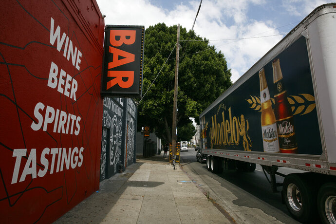 A truck with a beer advertisement stops in front of a bar in Los Angeles, Monday, June 29, 2020. California Gov. Gavin Newsom on Sunday ordered bars that have opened in seven California counties, including Los Angeles, to immediately close and urged bars in eight other counties to do the same, saying the coronavirus was rapidly spreading in those parts of the state and that bar settings create a higher risk of transmission. (AP Photo/Jae C. Hong)