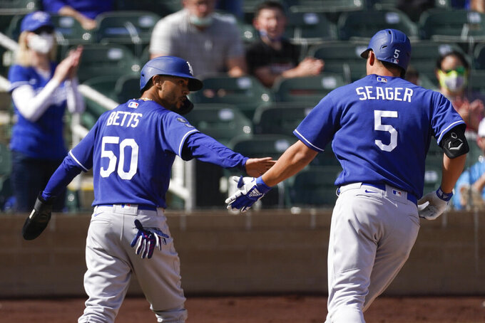 Los Angeles Dodgers' Corey Seager (5) gets a high-five from Mookie Betts (50) after Seager hit a home run during the fourth inning of a spring training baseball against the Colorado Rockies game Monday, March 15, 2021, in Scottdale, Ariz. Betts also scored. (AP Photo/Ashley Landis)