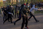 Left-wing protesters clash with police in Madrid's Vallecas neighborhood, Spain, Wednesday, April 7, 2021. Spanish police have used batons to keep protesters away from a campaign event of the far-right Vox party in Madrid. Scuffles started Wednesday when Santiago Abascal, the national leader of Vox, approached a crowd gathered to protest the party rally in Madrid's Vallecas neighborhood, a traditional left-wing bastion. Riot peace charged the bunches of protesters to keep them away from the party campaign event for upcoming regional elections. (AP Photo/Bernat Armangue)
