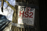 A protest sign is displayed on a tree by a roadside protest camp across the street from a High Speed 2 (HS2) rail line compound near the village of Harefield in north west London, Tuesday, Feb. 11, 2020. Britain's Conservative government is set to approve a contentious, expensive plan for a high-speed rail line linking London with central and northern England, despite opposition from environmentalists and even some members of the governing party. (AP Photo/Matt Dunham)