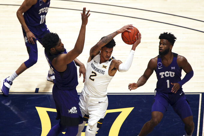 West Virginia forward Jalen Bridges (2) passes while defended by TCU center Kevin Samuel (21) and guard Mike Miles (1) during the first half of an NCAA college basketball game Thursday, March 4, 2021, in Morgantown, W.Va. (AP Photo/Kathleen Batten)