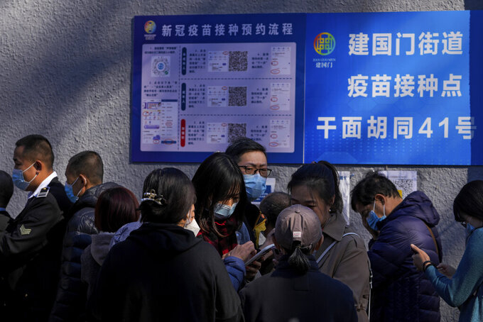 A group of women wearing face masks to help curb the spread of the coronavirus use their smartphone to make appointment as residents line up to receive booster shots against COVID-19 at a vaccination site near a residential area in Beijing, Friday, Oct. 22, 2021. China's capital Beijing has begun offering booster shots against COVID-19, four months before the city and surrounding regions are to host the Winter Olympics. (AP Photo/Andy Wong)