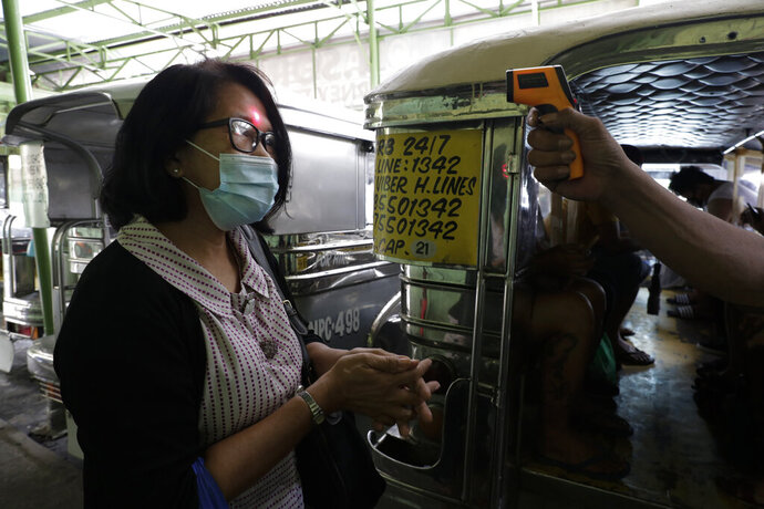 A woman's temperature is measured before riding a passenger jeepney to help curb the spread of COVID19 as drivers at the Tandang Sora terminal were recently allowed back on the road after months of not being able to work on Sunday, Aug. 2, 2020 in Quezon city, Philippines. Coronavirus infections in the Philippines continues to surge Sunday as medical groups declared the country was waging a losing battle against the contagion and asked the president to reimpose a lockdown in the capital. (AP Photo/Aaron Favila)