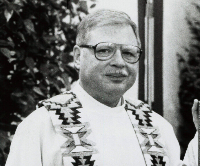 FILE - This 1989 file photo shows Father Arthur Perrault in Albuquerque, N.M. The former Roman Catholic priest found guilty of aggravated sexual abuse in New Mexico is scheduled to be sentenced Friday, Sept. 13, 2019, in Santa Fe. Federal prosecutors are requesting a sentence of more than 30 years in prison for Perrault, once a pastor at an Albuquerque parish and a chaplain at Kirtland Air Force Base. The 81-year-old maintained his innocence throughout his trial in April. (The Albuquerque Journal via AP, File)