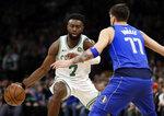 Boston Celtics guard Jaylen Brown (7) makes a dribble move against Dallas Mavericks forward Luka Doncic (77) during the first quarter of an NBA basketball game Friday, Jan. 4, 2019, in Boston. (AP Photo/Elise Amendola)
