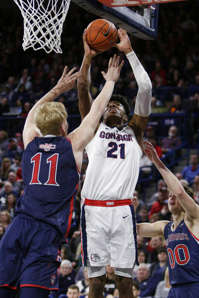 Gonzaga forward Rui Hachimura (21) shoots between Saint Mary's forward Matthias Tass (11) and guard Tanner Krebs (0) during the first half of an NCAA college basketball game in Spokane, Wash., Saturday, Feb. 9, 2019. (AP Photo/Young Kwak)