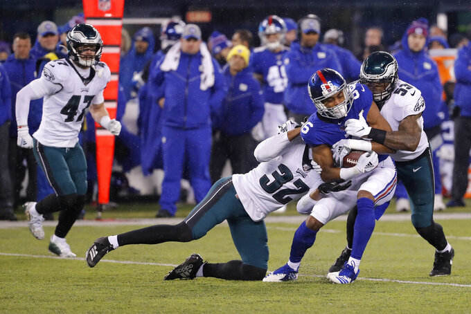 New York Giants wide receiver Darius Slayton (86) is stopped by Philadelphia Eagles cornerback Rasul Douglas (32) and Eagles outside linebacker Nigel Bradham (53) in the first half of an NFL football game, Sunday, Dec. 29, 2019, in East Rutherford, N.J. (AP Photo/Seth Wenig)