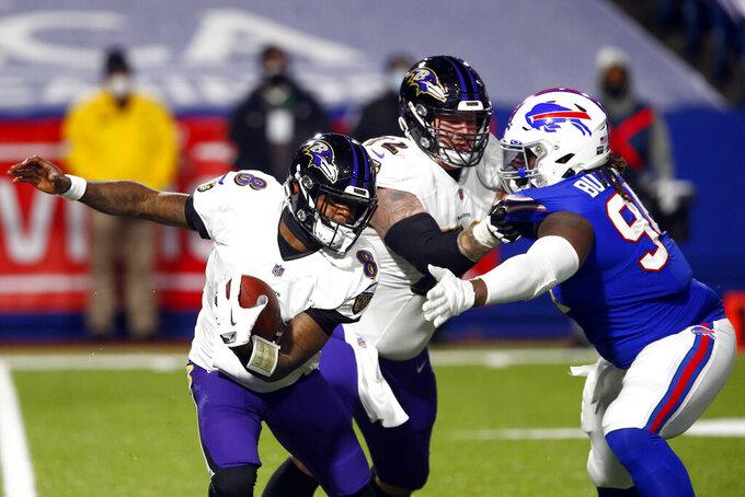 Baltimore Ravens quarterback Lamar Jackson, left, rushes past Buffalo Bills' Vernon Butler, right, as teammate Ben Powers (72) blocks him during the first half of an NFL divisional round football game Saturday, Jan. 16, 2021, in Orchard Park, N.Y. (AP Photo/John Munson)