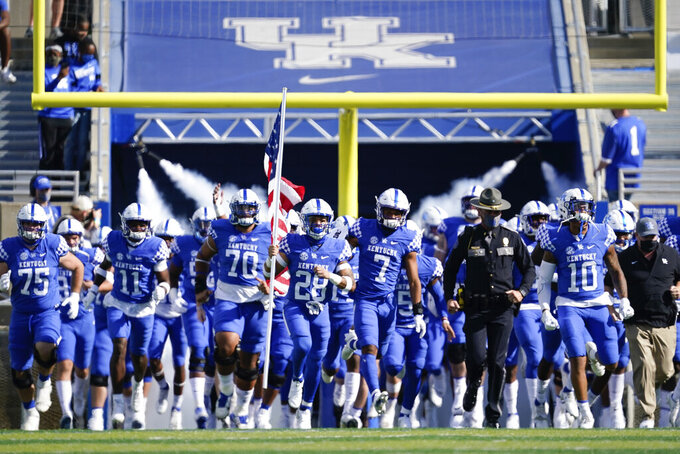 Kentucky players run onto the field before an NCAA college football game against Mississippi, Saturday, Oct. 3, 2020, in Lexington, Ky. (AP Photo/Bryan Woolston)