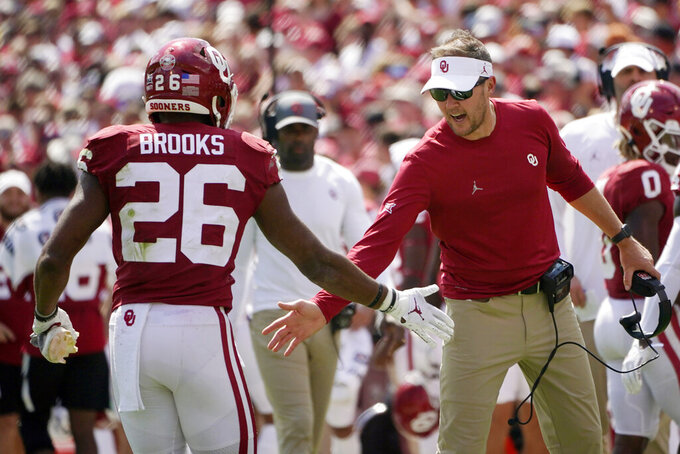 Oklahoma head coach Lincoln Riley, right, greets running back Kennedy Brooks (26) as Brooks returns to the sidelines following a touchdown against Nebraska in the second half of an NCAA college football game, Saturday, Sept. 18, 2021, in Norman, Okla. (AP Photo/Sue Ogrocki)