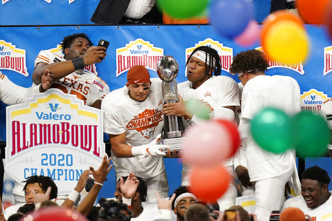 Texas players celebrate a win over Colorado in the Alamo Bowl NCAA college football game, early Wednesday, Dec. 30, 2020, in San Antonio. (AP Photo/Eric Gay)