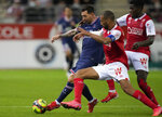 PSG's Lionel Messi, left, challenges for the ball with Reims' Yunis Abdelhamid during the France League One soccer match between Reims and Paris Saint-Germain, at the Stade Auguste-Delaune in Reims, France, Sunday, Aug. 29, 2021. (AP Photo/Francois Mori)