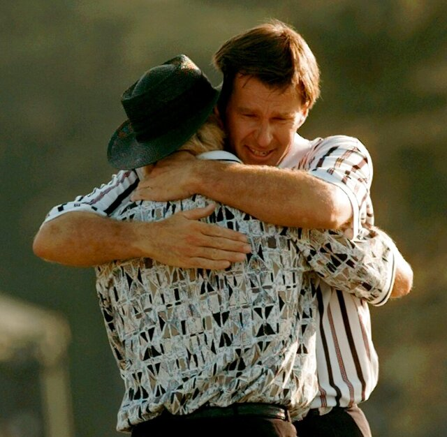 FILE - In this April 14, 1996, file photo, Nick Faldo hugs Greg Norman, left, as they finish up on the 18th hole of the Masters golf tournament at Augusta National Golf Club in Augusta, Ga. Faldo came from behind to beat Norman by five strokes to win his third Masters. (AP Photo/Dave Martin, File)