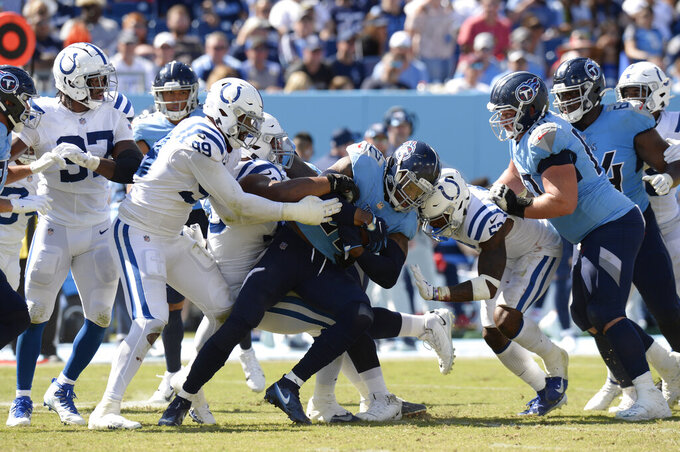 Tennessee Titans running back Derrick Henry (22) is stopped by Indianapolis Colts defensive tackle DeForest Buckner (99) in the second half of an NFL football game Sunday, Sept. 26, 2021, in Nashville, Tenn. (AP Photo/Mark Zaleski)