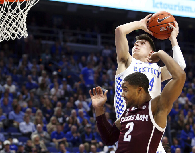 Kentucky's Tyler Herro, top, goes up for a dunk near Texas A&M's TJ Starks (2) during the first half of an NCAA college basketball game in Lexington, Ky., Tuesday, Jan. 8, 2019. (AP Photo/James Crisp)